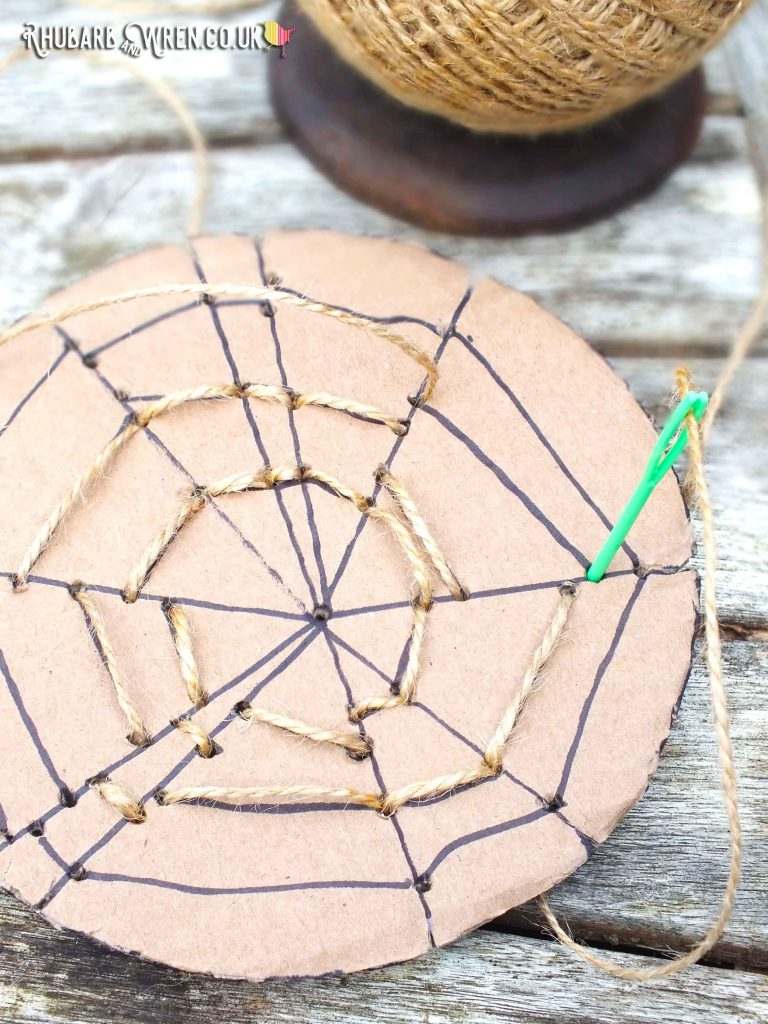 Cardboard spiderweb for threading - concentric rings threaded with string and needle half in.