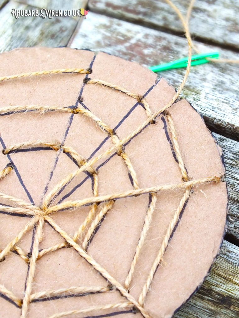 Cardboard Spiderweb - string threaded through holes along lines.