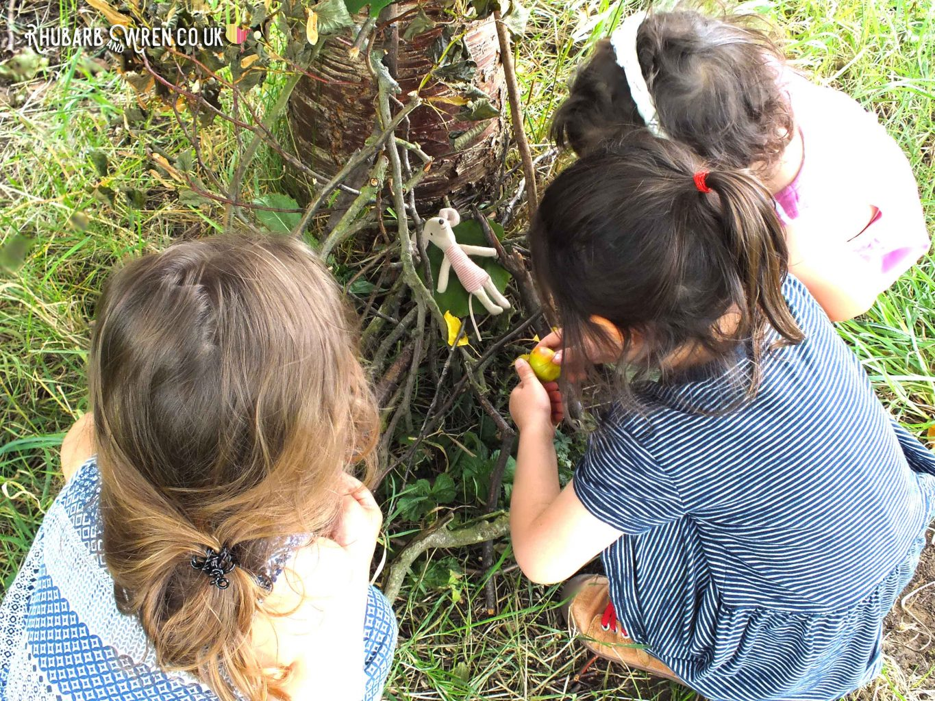 three preschool girls gathered around toy mouse and mini den under a tree