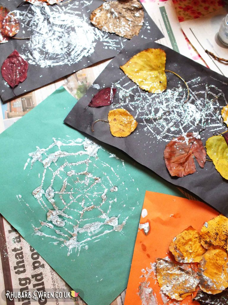 Green, black and orange paper printed with silver spiderwebs