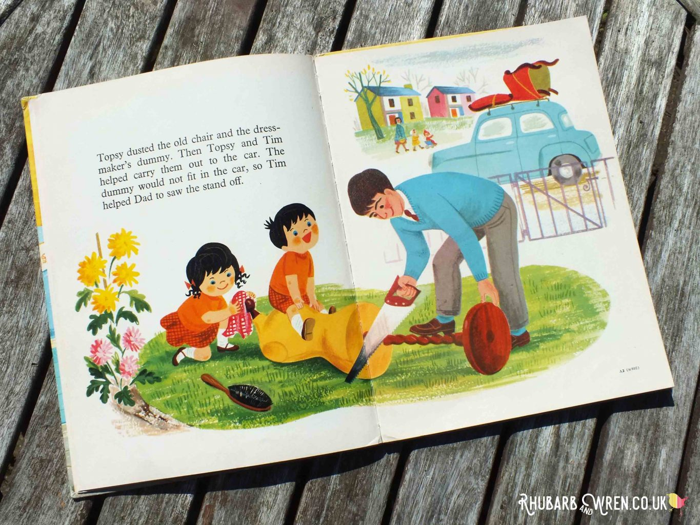 Double-page spread in Topsy and Tim's Bonfire Night, showing Dad sawing off off base of dressmaker's dummy while the twins watch.