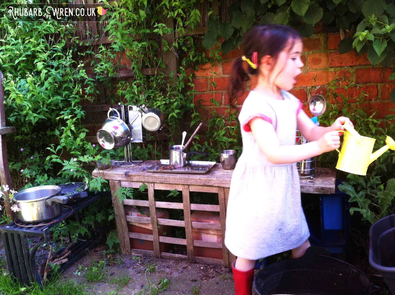 girl playing in mud kitchen, holding a yellow watering can