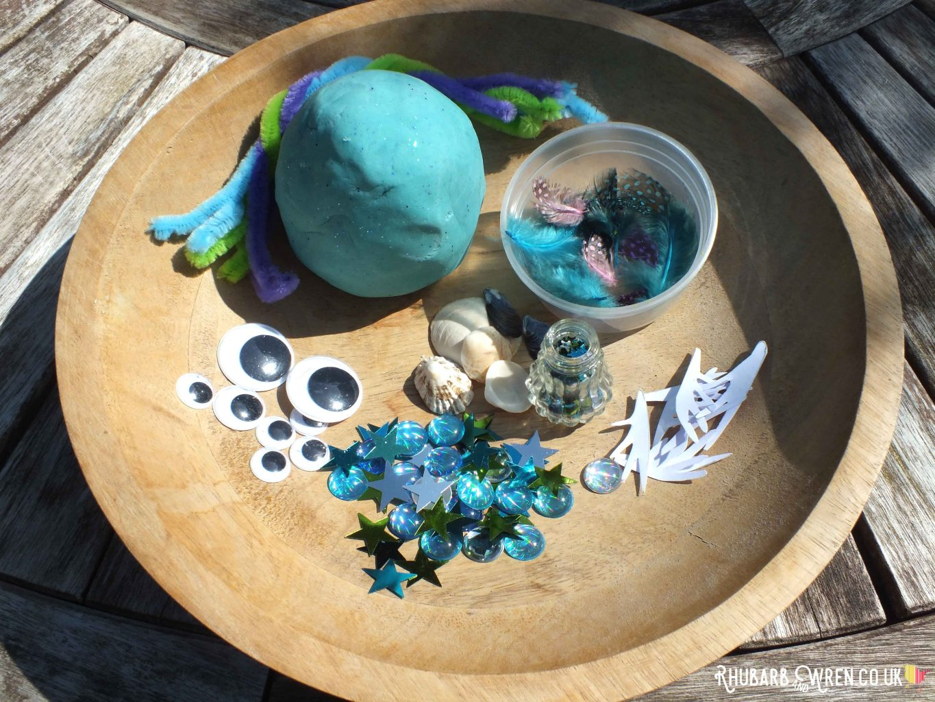 home-made play dough and decorations in a wooden bowl