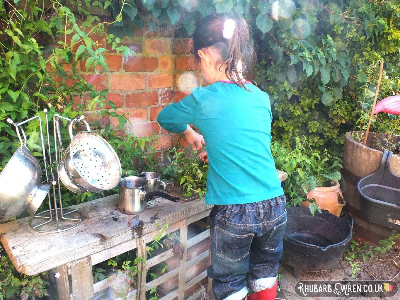 little girl playing in mud kitchen