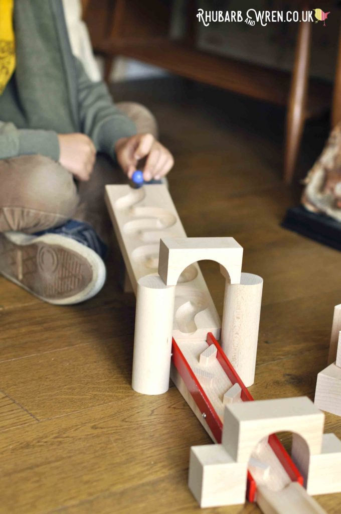 Boy placing marble on sloped wooden winding marble run track