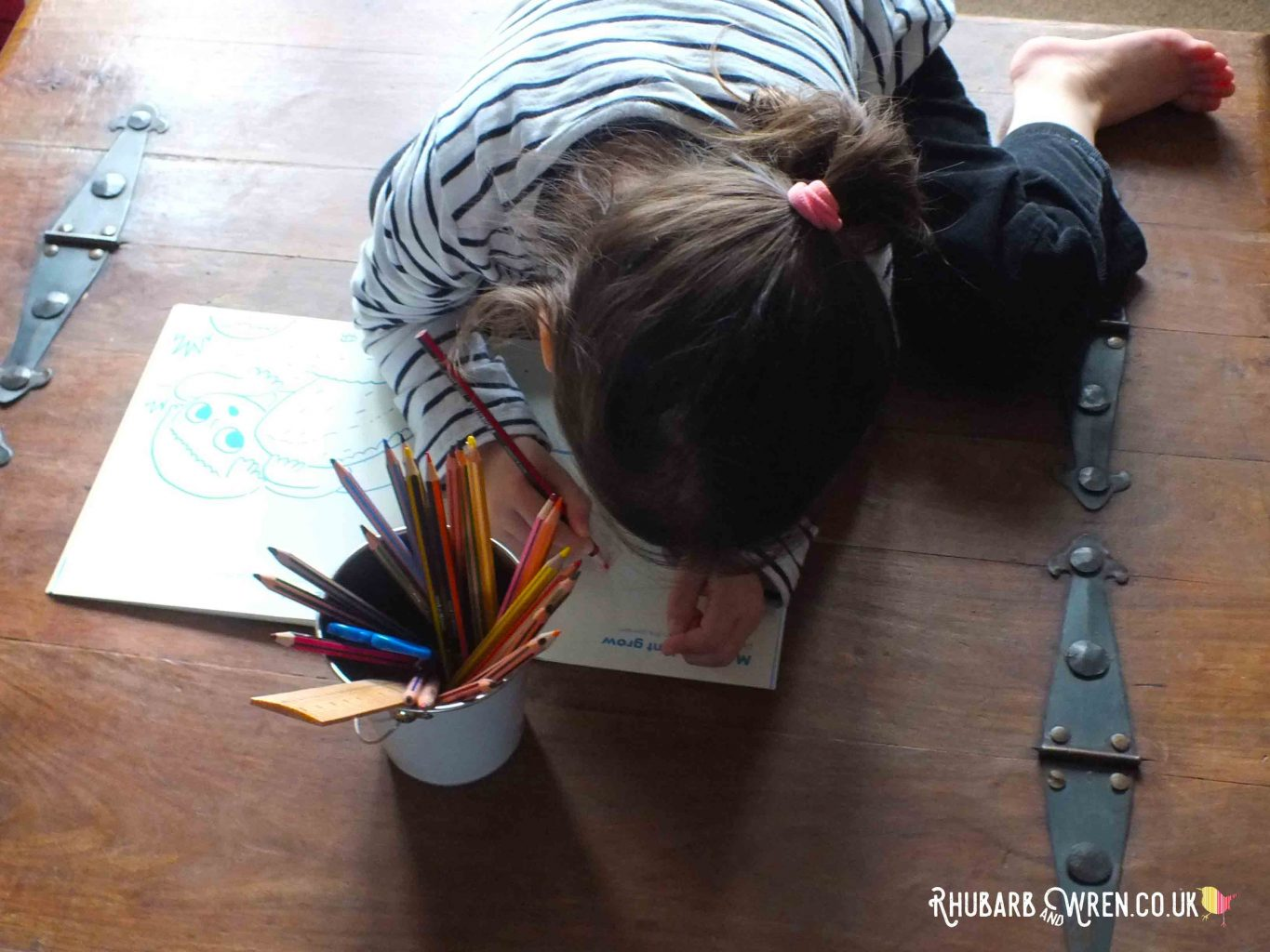 Child colouring in Okido magazine page, with big pot of pencils