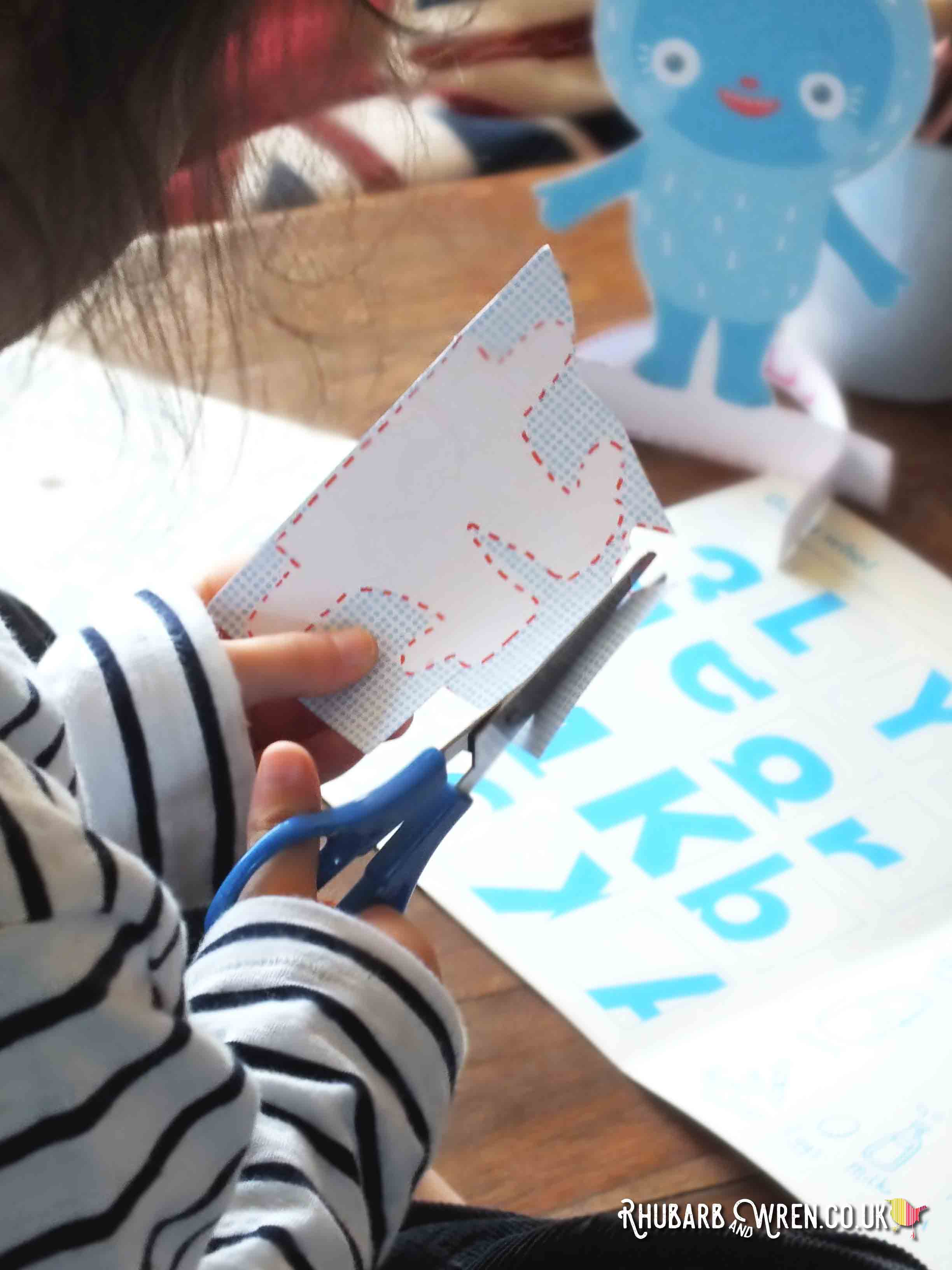 Child cutting out paper shapes from Okido magazine with scissors