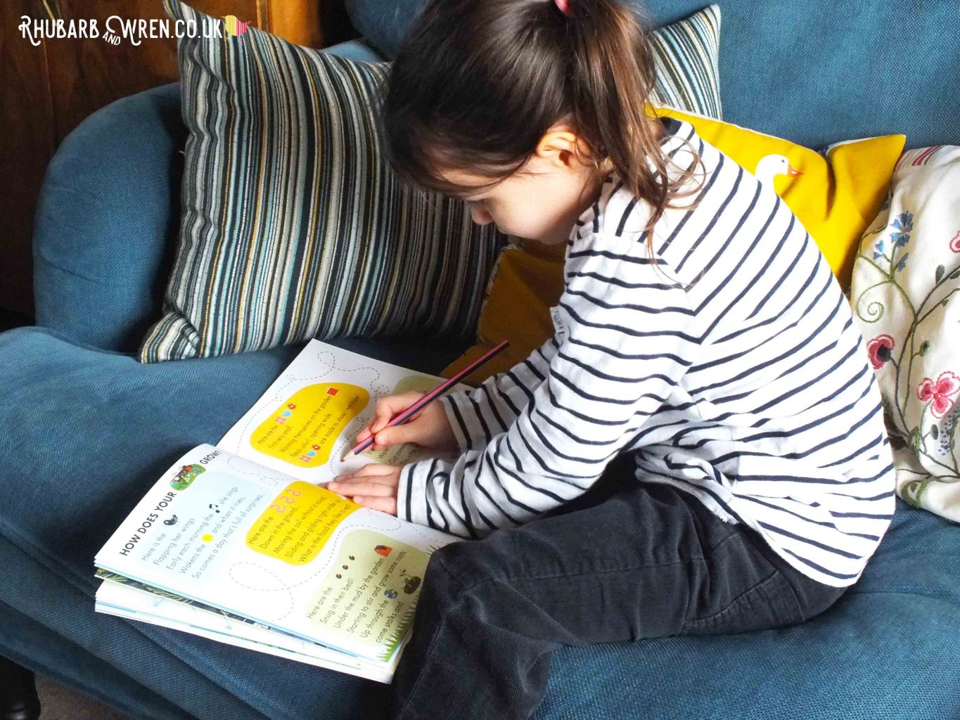 Child sat on sofa, writing in Okido magazine