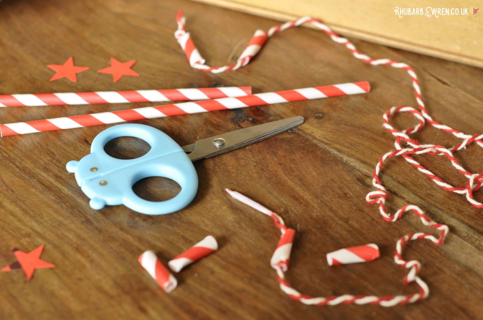 Scissors, paper straws, sections of straw and string for threading