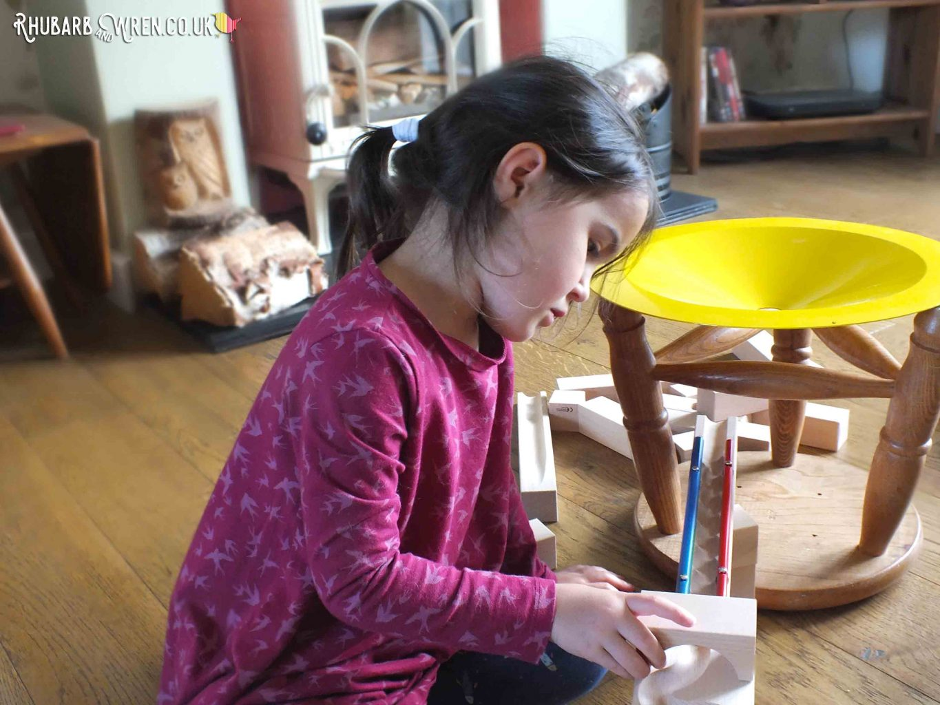 Girl placing wooden bridge piece onto marble run track
