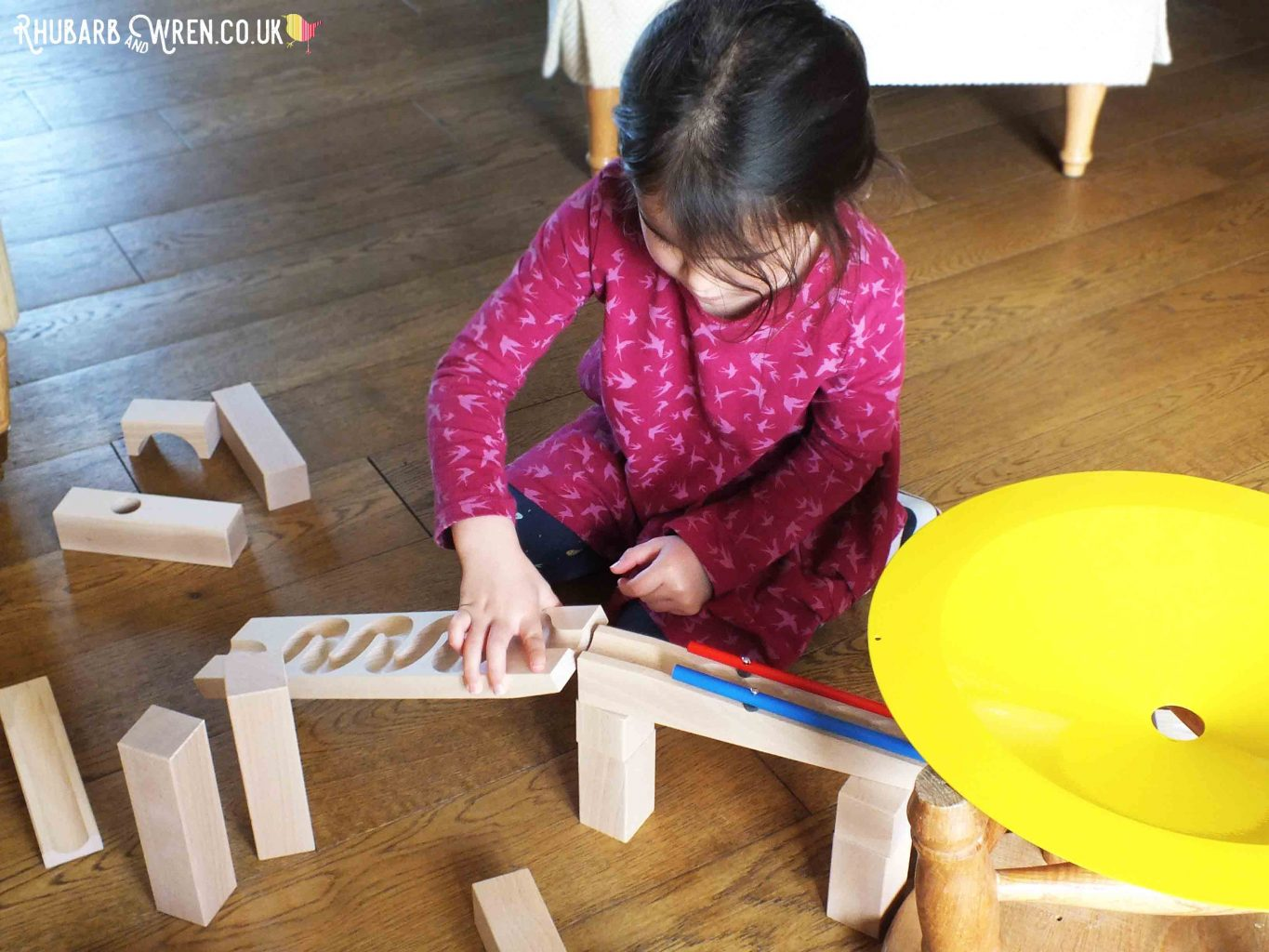 Girl building HABA wooden marble run