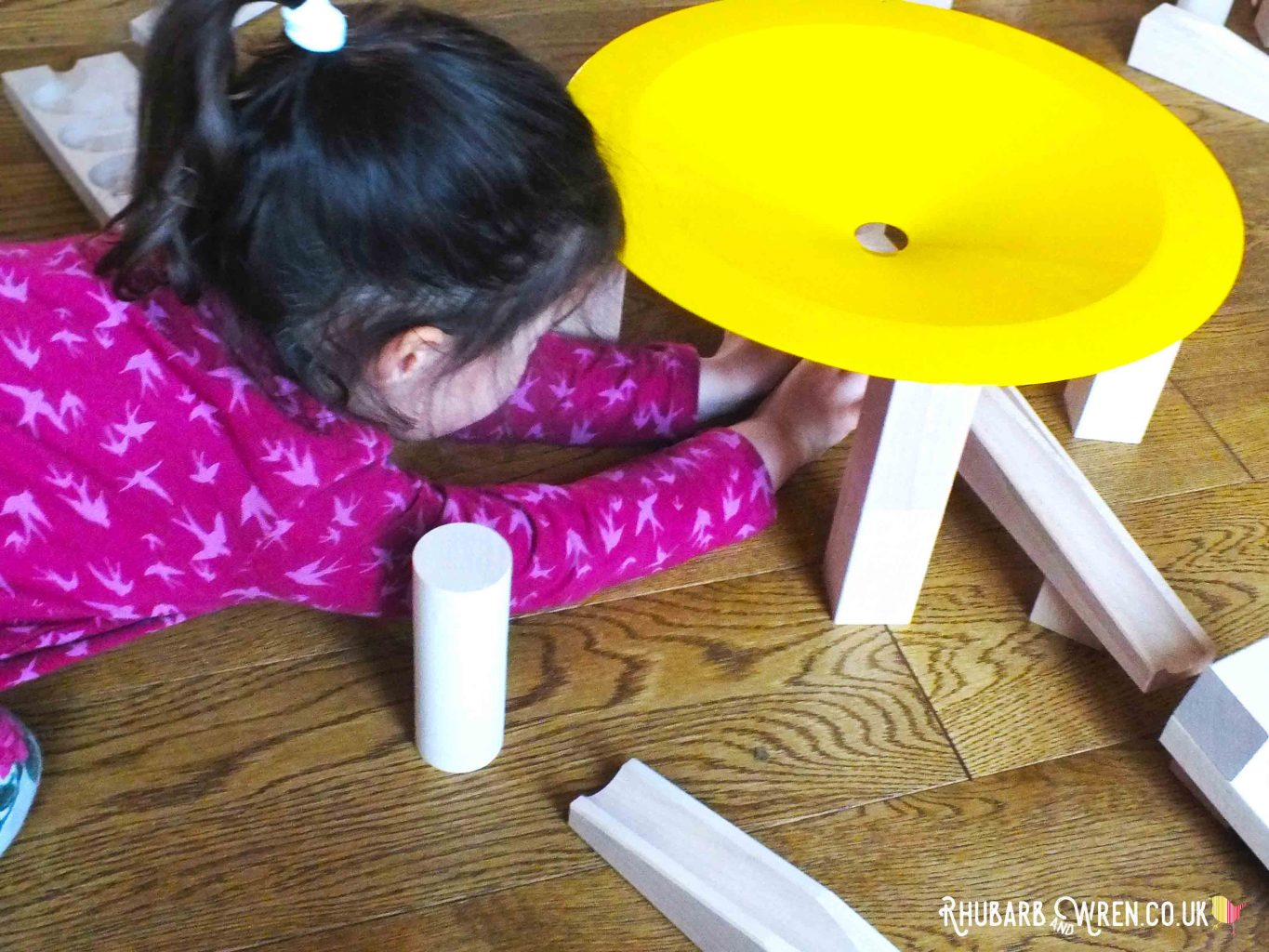 Girl lying down and stretching under whirlpool section to set up HABA wooden marble run