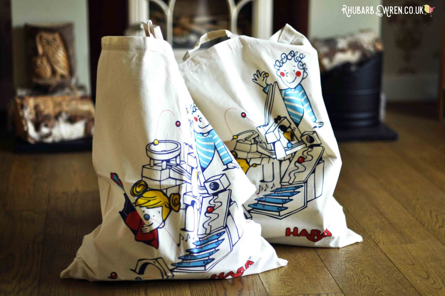 Two full, large canvas bags with carton images of children buidling HABA's wooden marble run