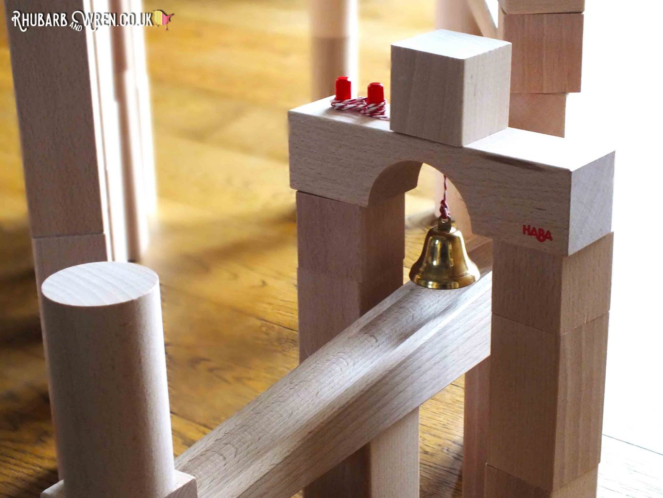 Small brass bell dangling from bridge section over HABA wooden marble run track
