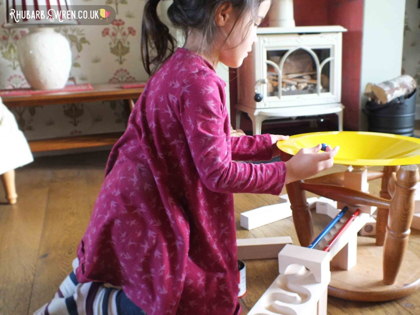 Girl launching marbles into whirlpool section of HABA marble run set.