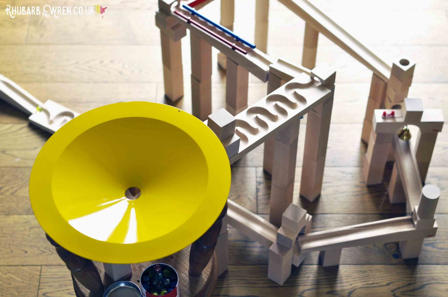 Looking down on wooden marble run including large yellow metal 'whirlpool' dish funnel