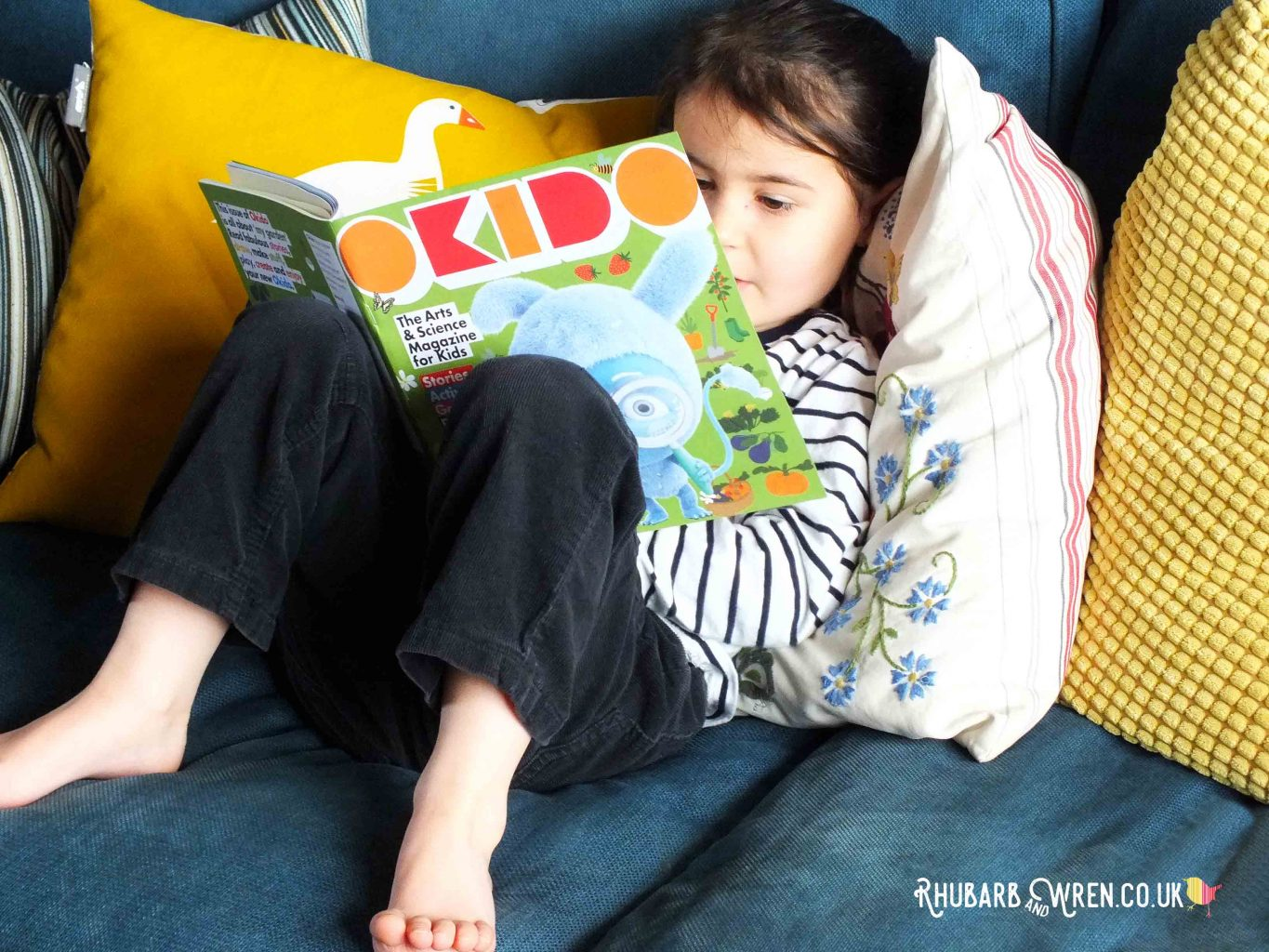 Preschool girl reading Okido magazine on blue sofa