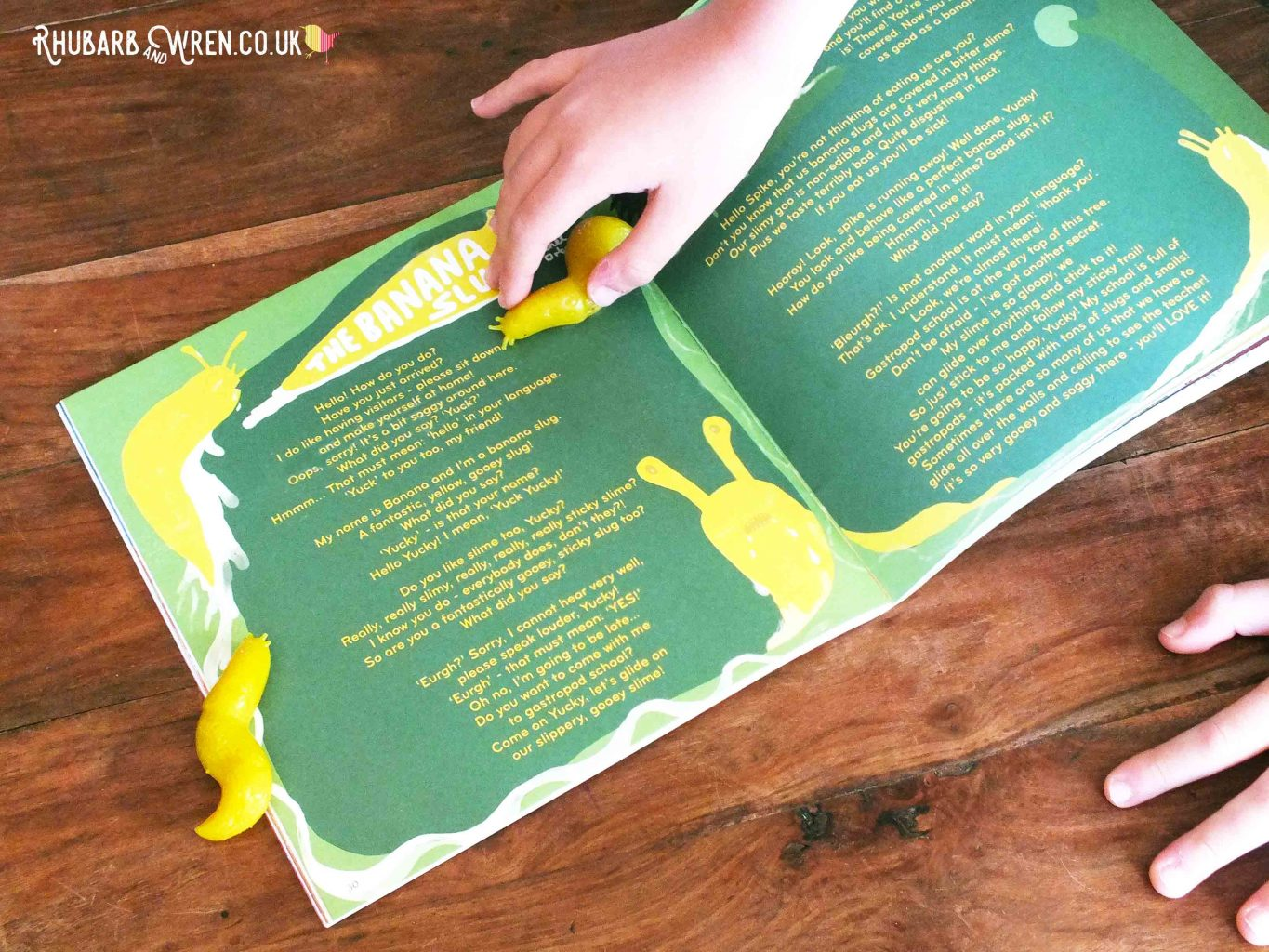 Okido magazine open to spread with 'Banana Slug' poem. Child's hand and rubber slug.