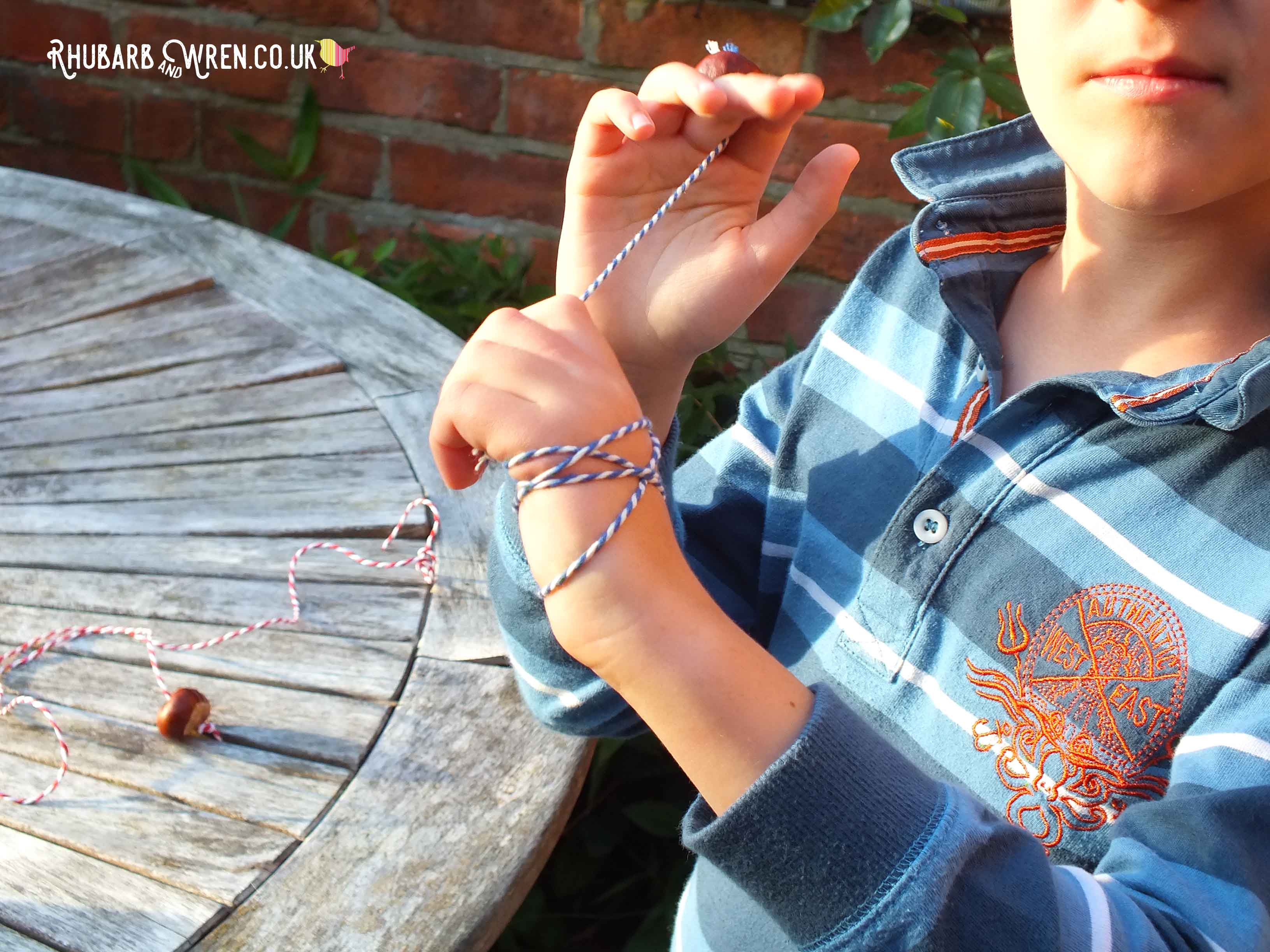 Boy playing conkers - holding horse chestnut threaded onto string.