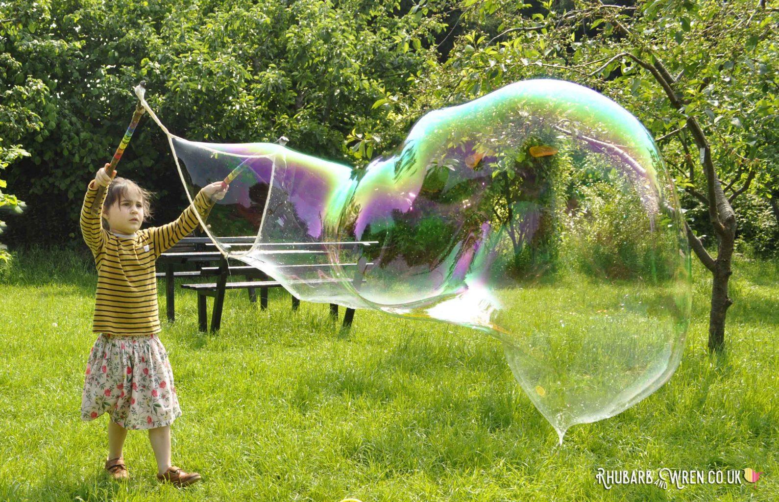 Child making giant bubbles with a diy giant bubble wand