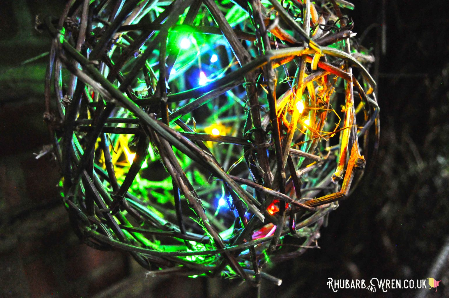 Close up of DIY twig ball lantern with multi-colour LED lights