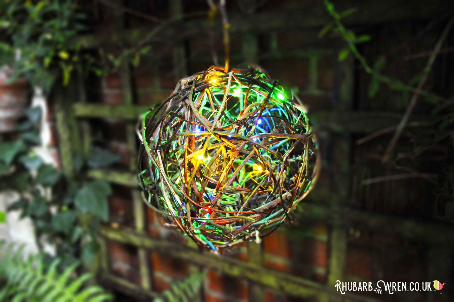 A colourful twig ball lantern hanging in the garden