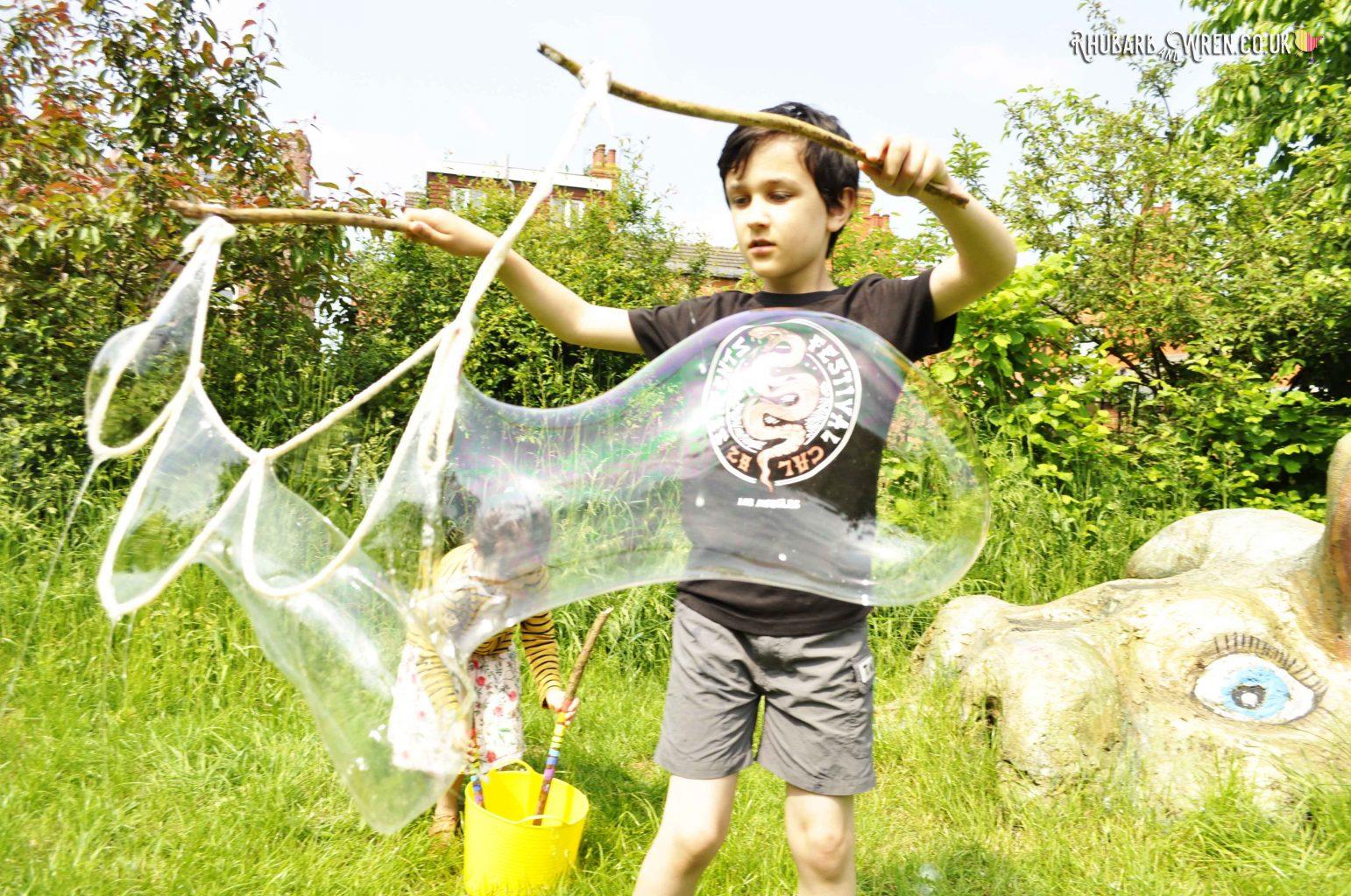 Boy making giant bubbles using a diy bubble mix recipe