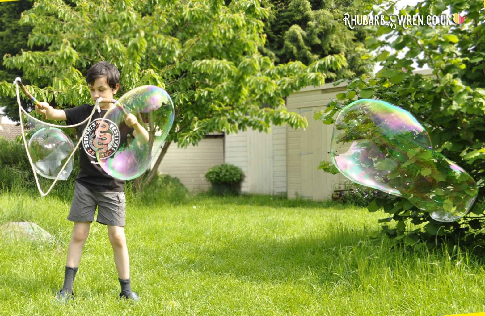 Boy making giant bubbles with home-made bubble mix recipe and wands