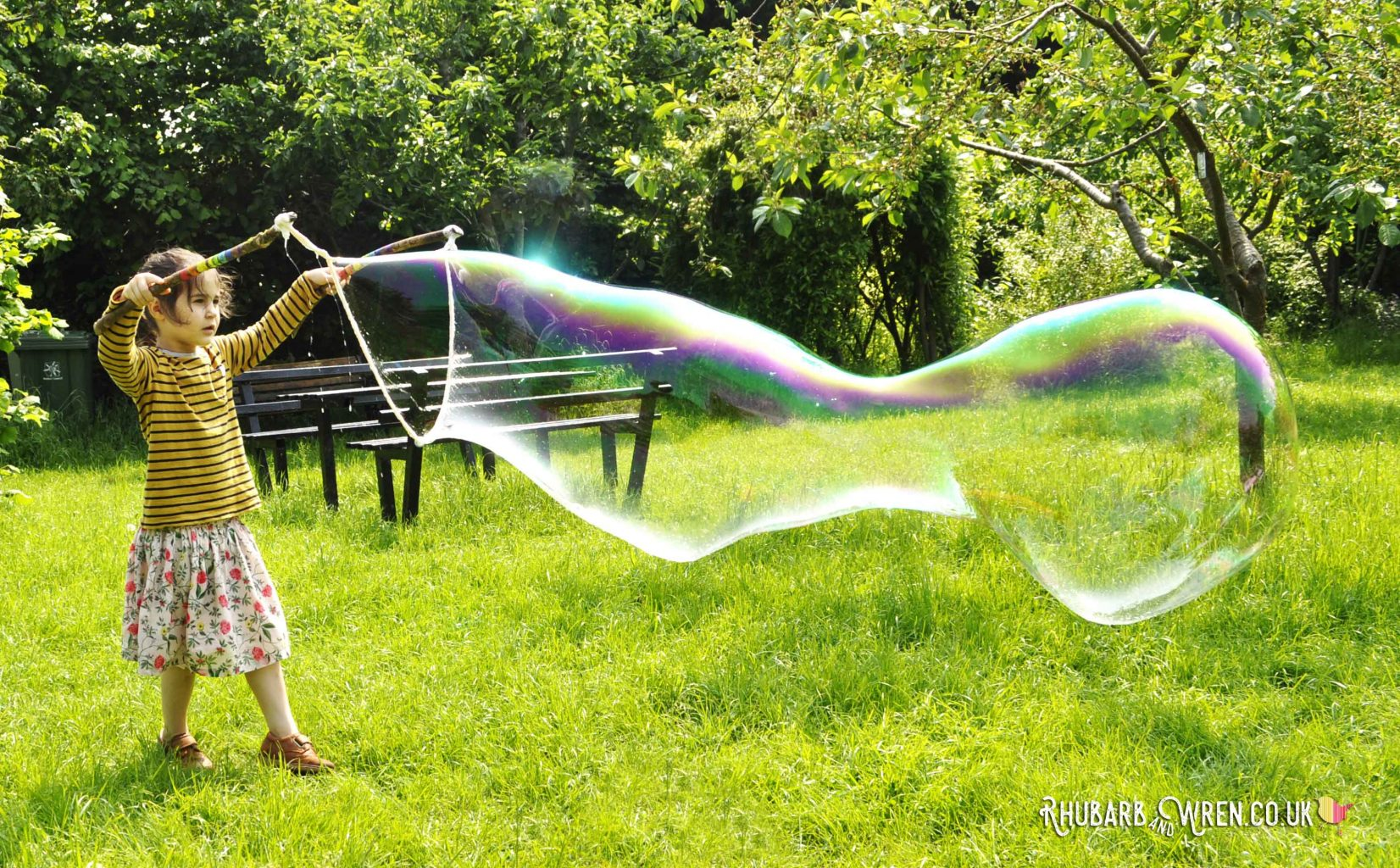 child making giant bubble with diy bubble mix recipe and wands
