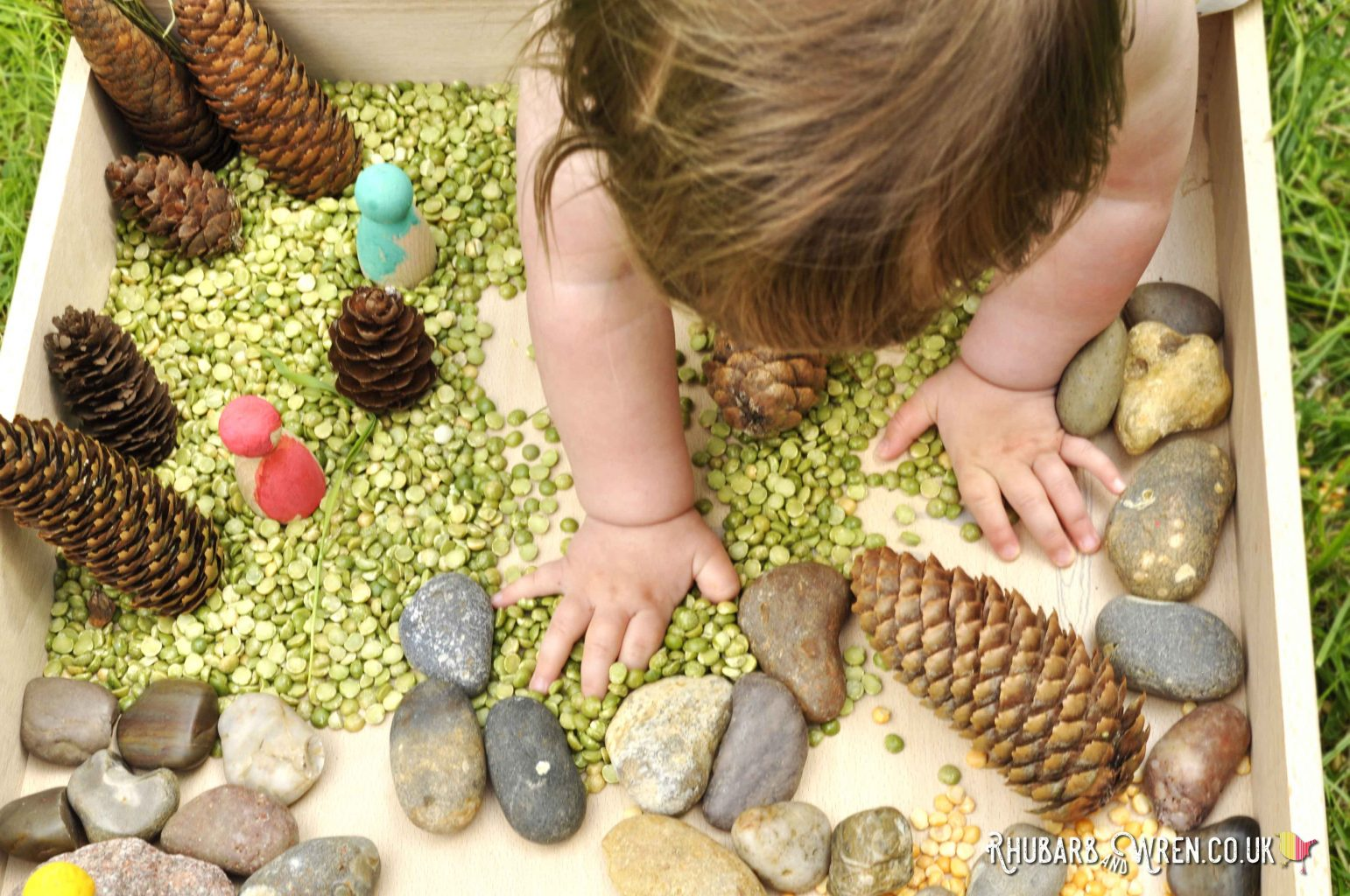 Baby playing with natural materials in Grapat free-play box