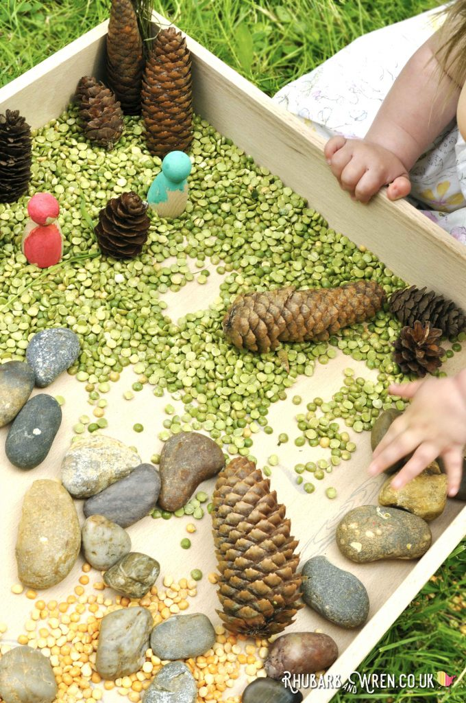 Baby touching pebbles in Grapat free-play box