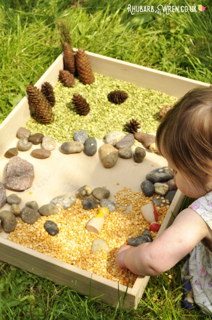 Baby grabbing dried peas in Grapat free-play box