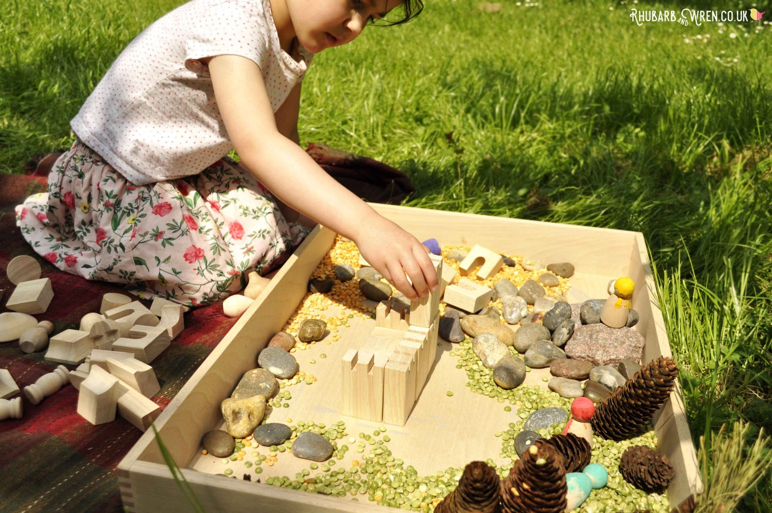 Child building a castle from blocks in Grapat free-play box