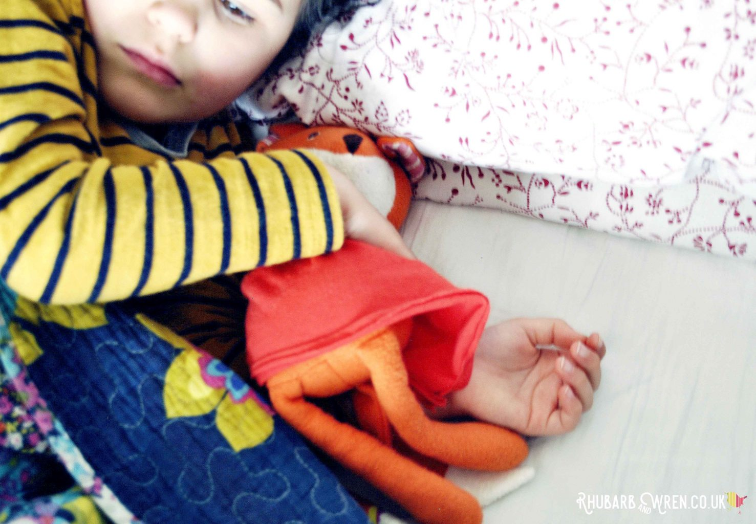 Girl cuddling Hazel Village soft toy, Flora Fox, in bed.