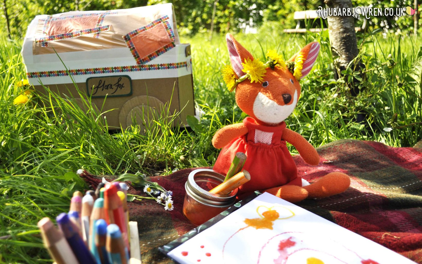 Hazel Village soft toy Flora Fox, next to pencils and drawing
