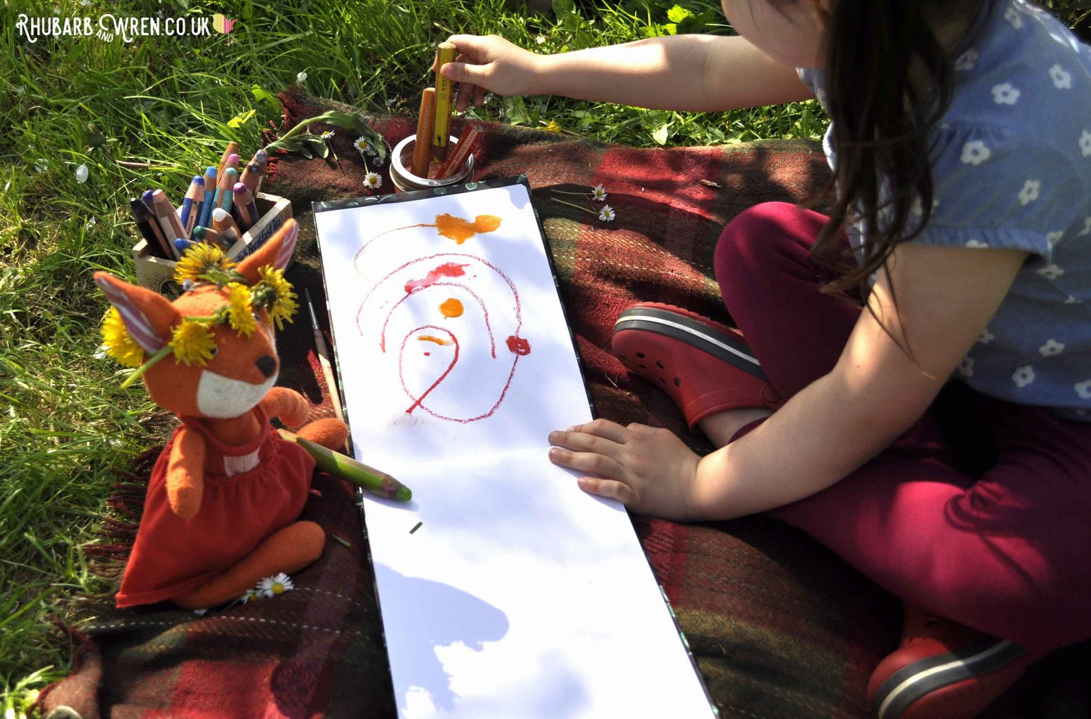 A child drawing next to Hazel Village soft toy - Flora Fox -