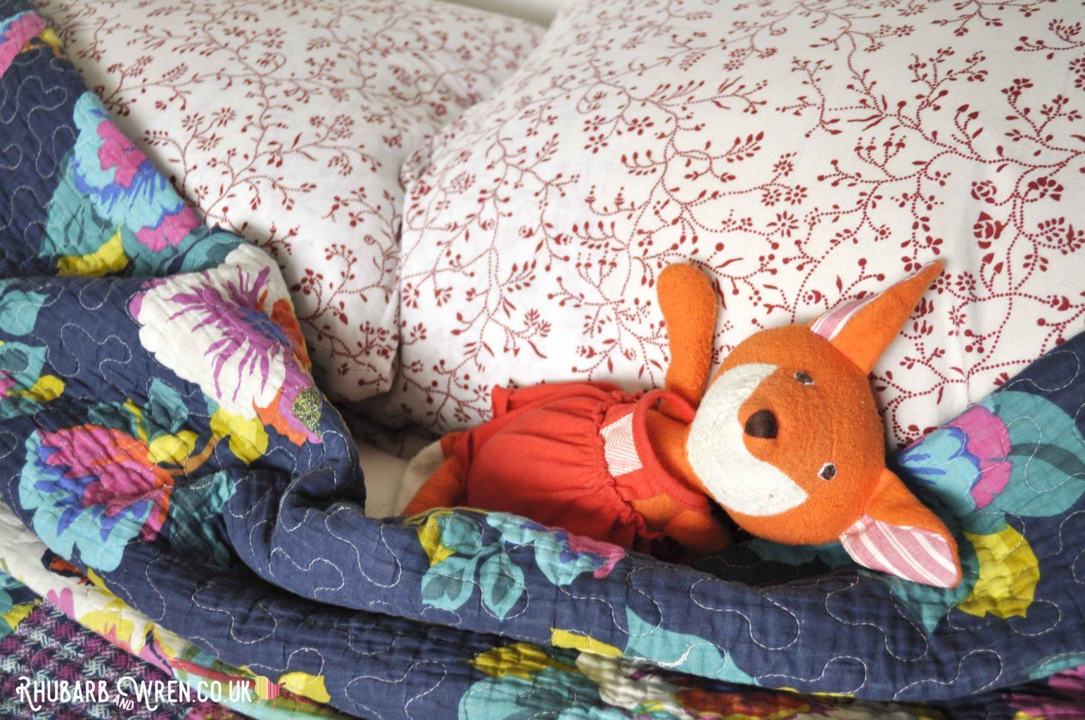 Hazel Village soft toy, Flora Fox, lying in a bed