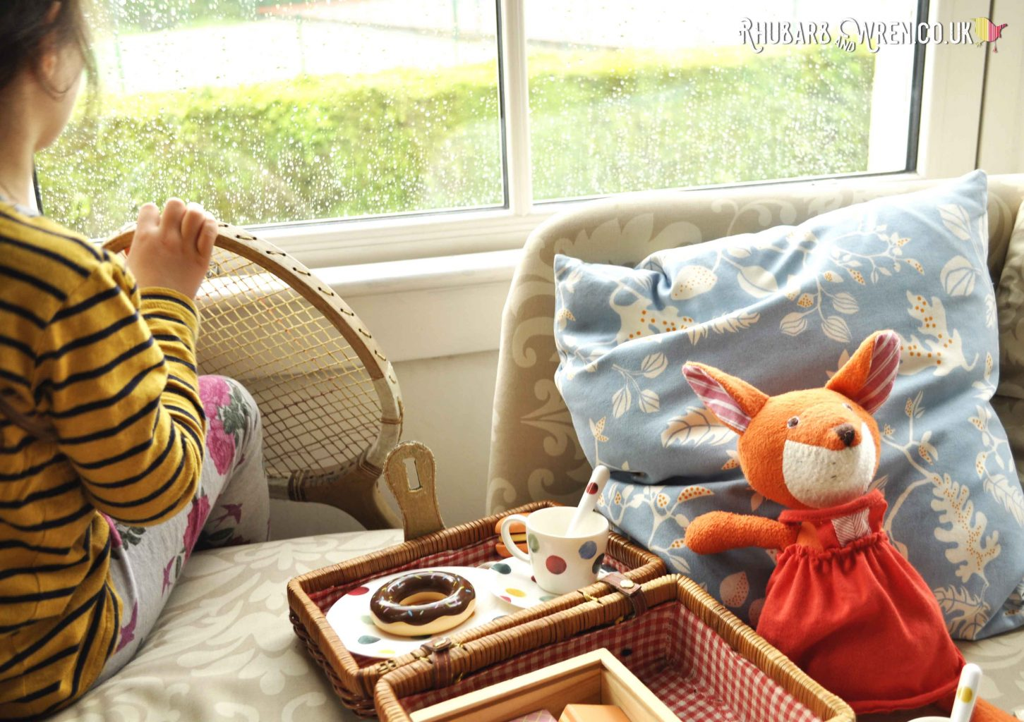 Girl looking out of window with Hazel Village soft toy fox