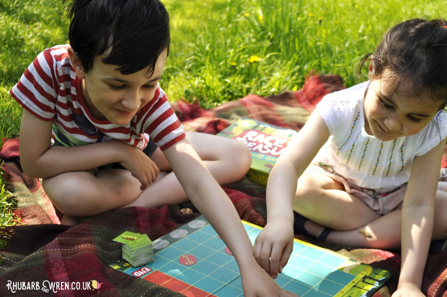 two children playing a Peaceable Kingdom board game - Race to the Treasure