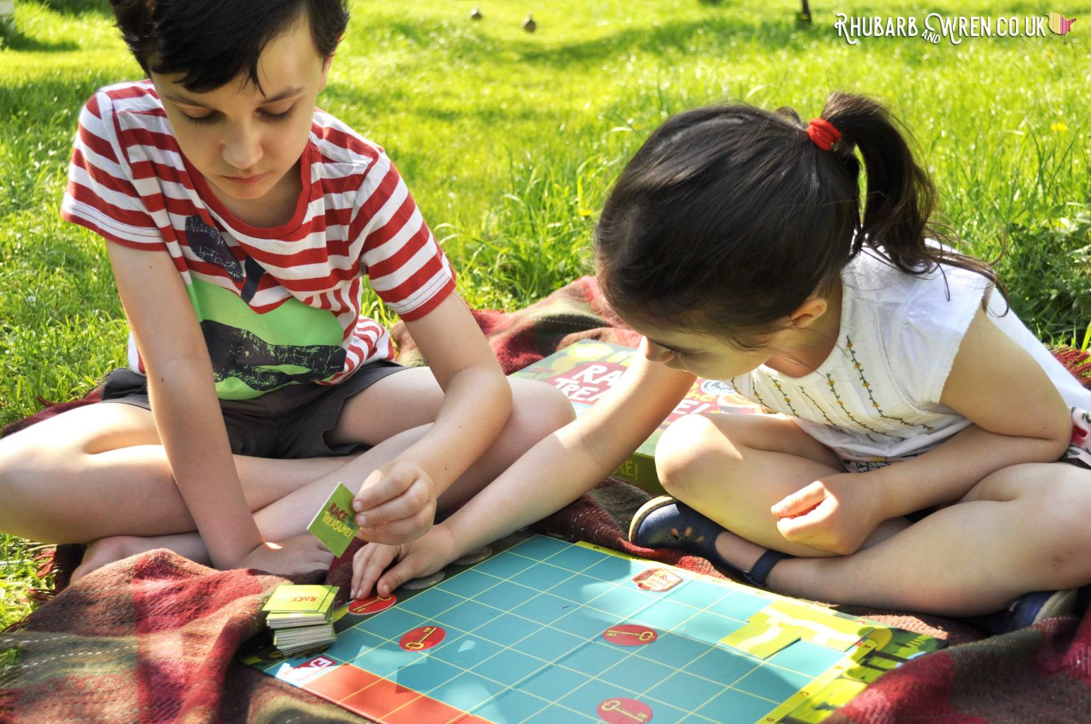 Children playing Peaceable Kingdom board game outside