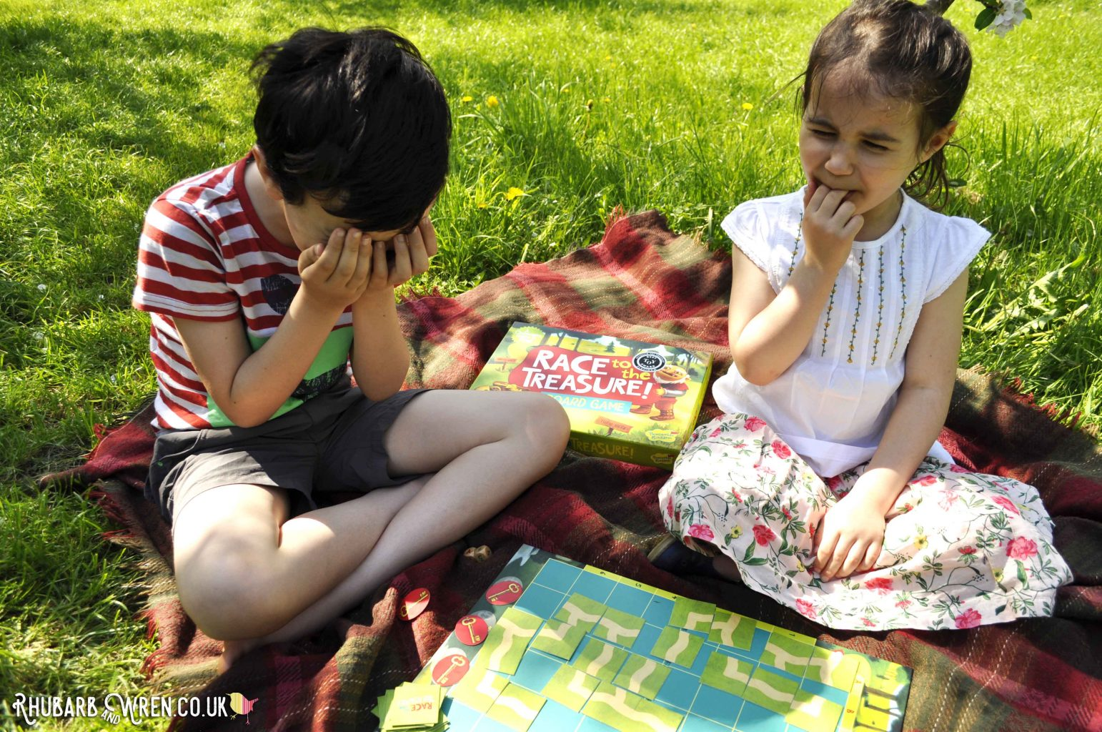 Children pulling sad faces playing Peaceable Kingdom board game