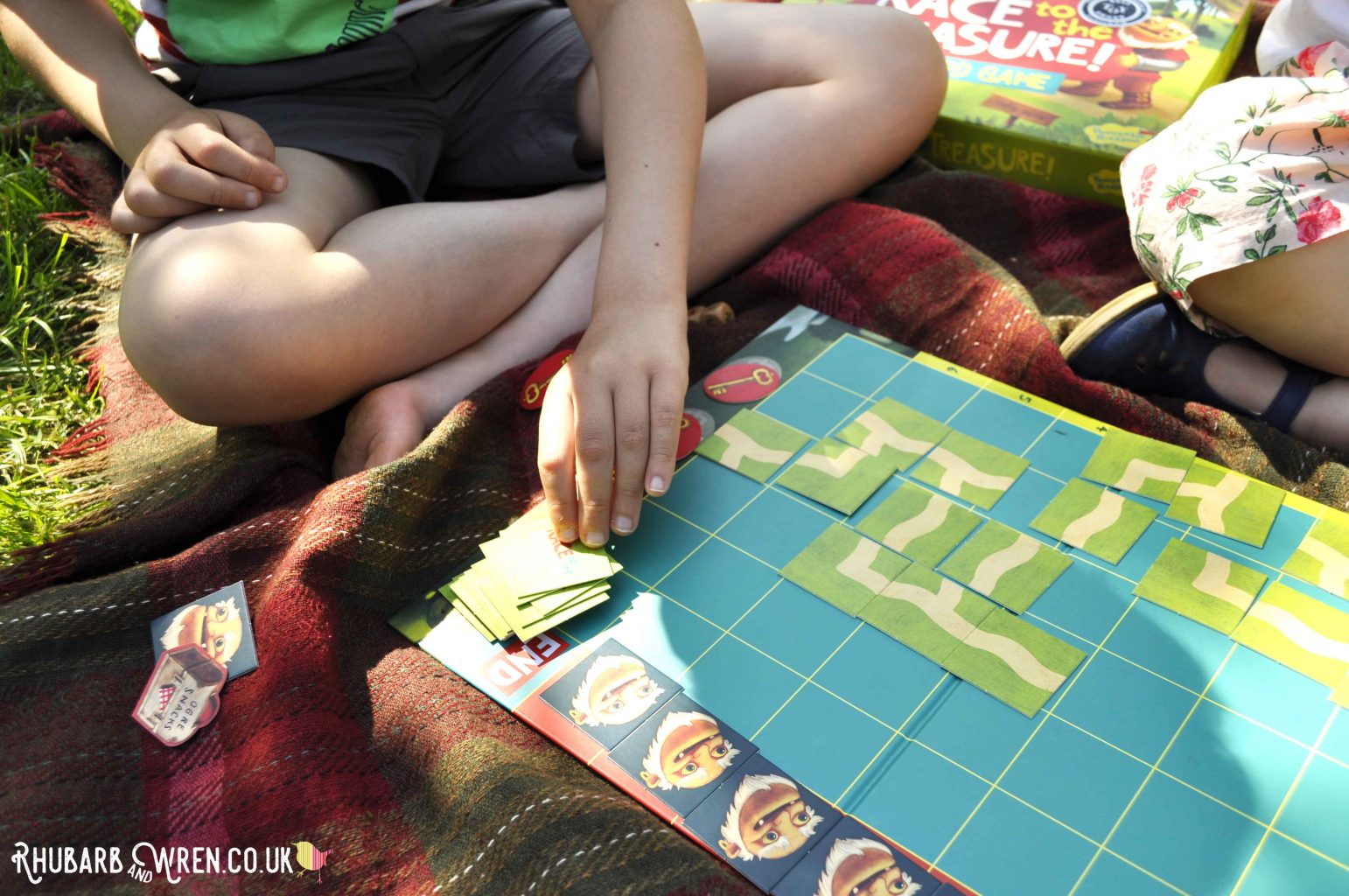 Close up of children playing Peaceable Kingdom board game - Race to the Treasure