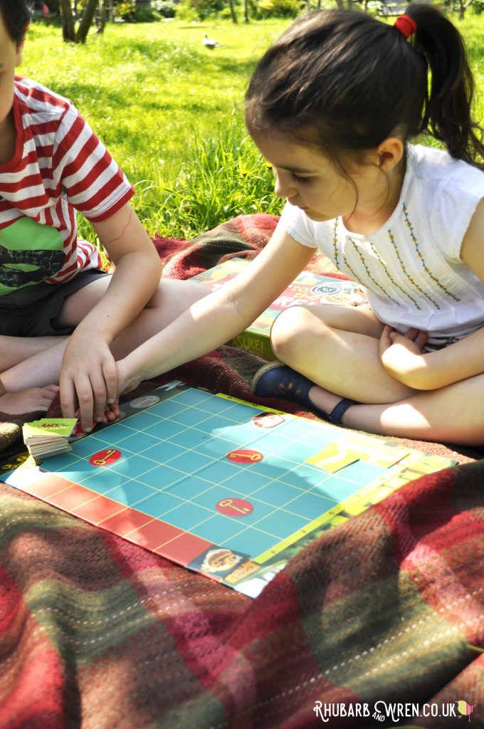 Girl playing Peaceable Kingdom board game 'Race to the Treasure'