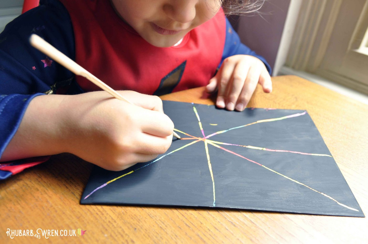 Child drawing on diy scratch art card