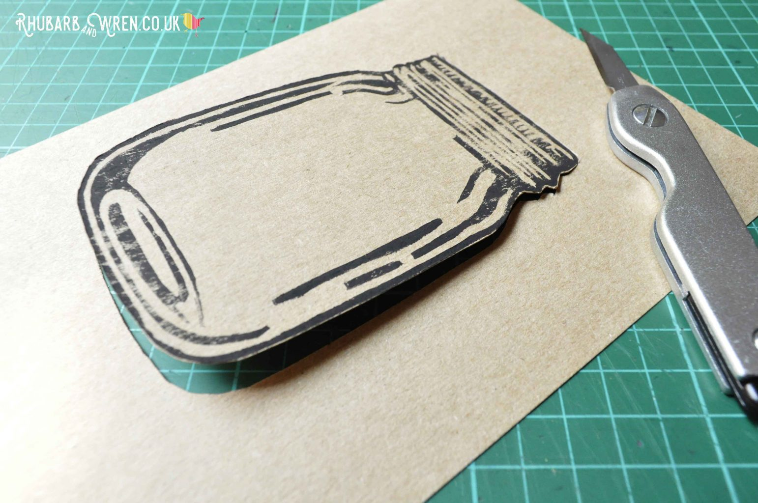 lino printed image of mason jar partially cut out.