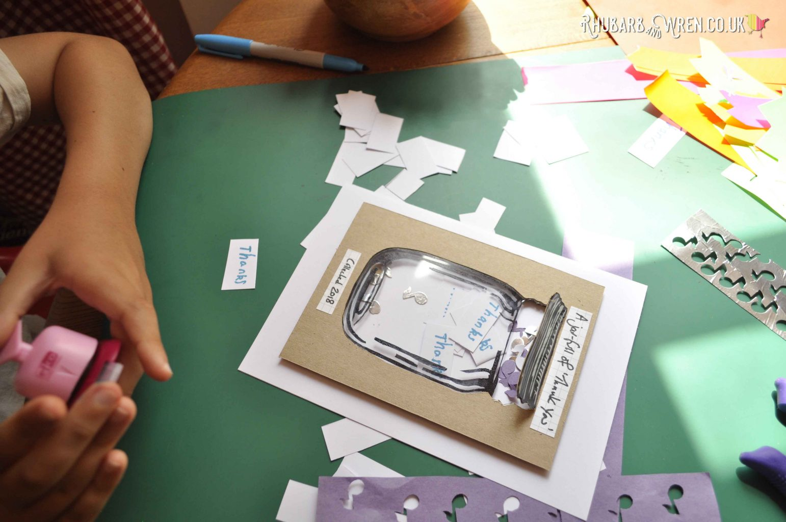 Child adding contents to DIY mason jar shaker card.