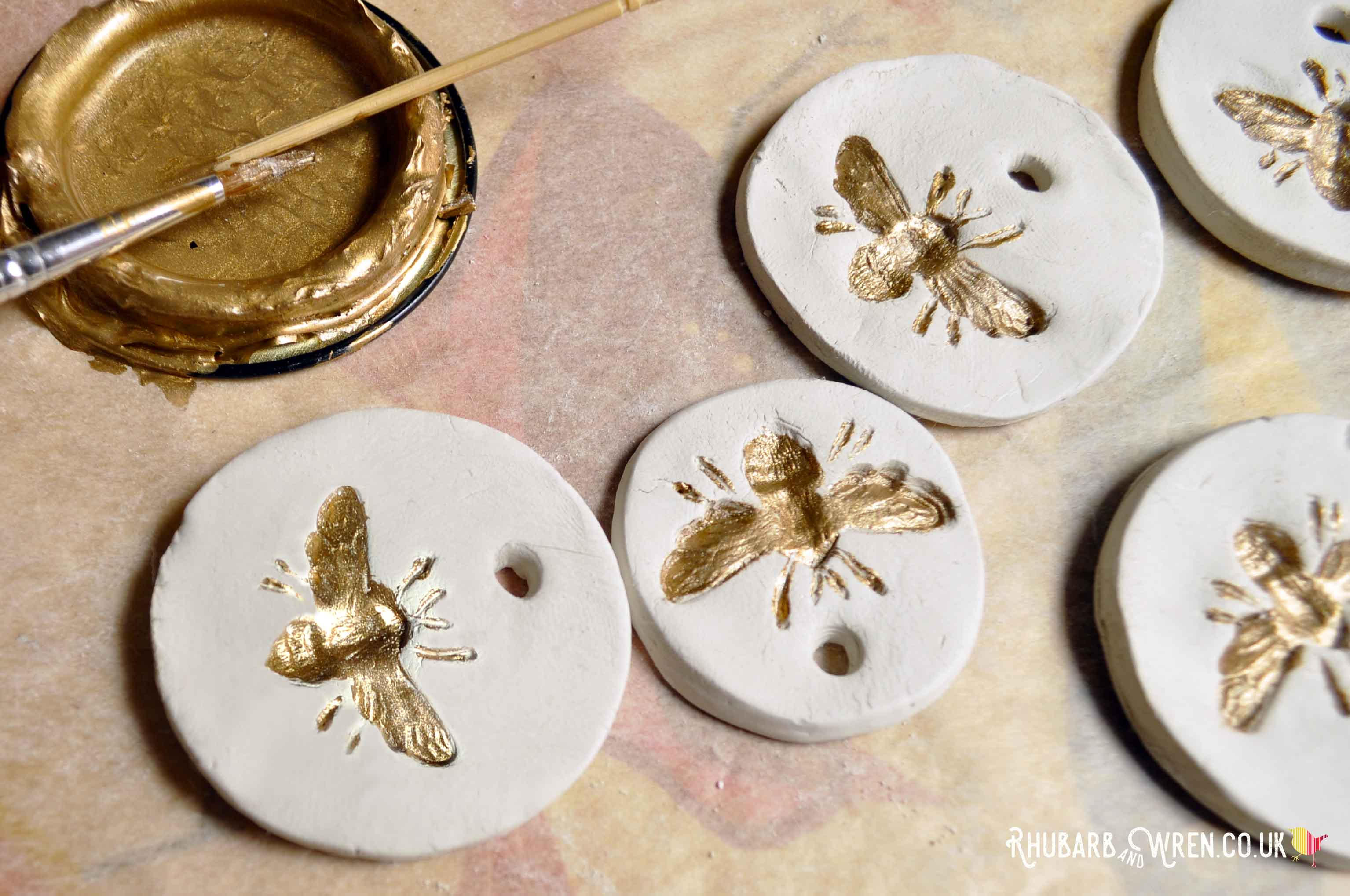 Painting gold bees on DIY air dry clay pendants