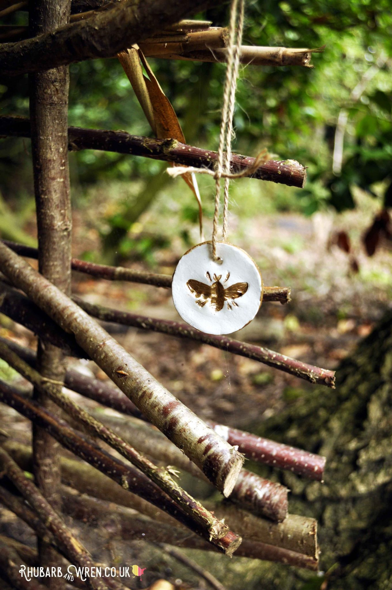 Gold bee pendant for treasure hunt hanging in woods
