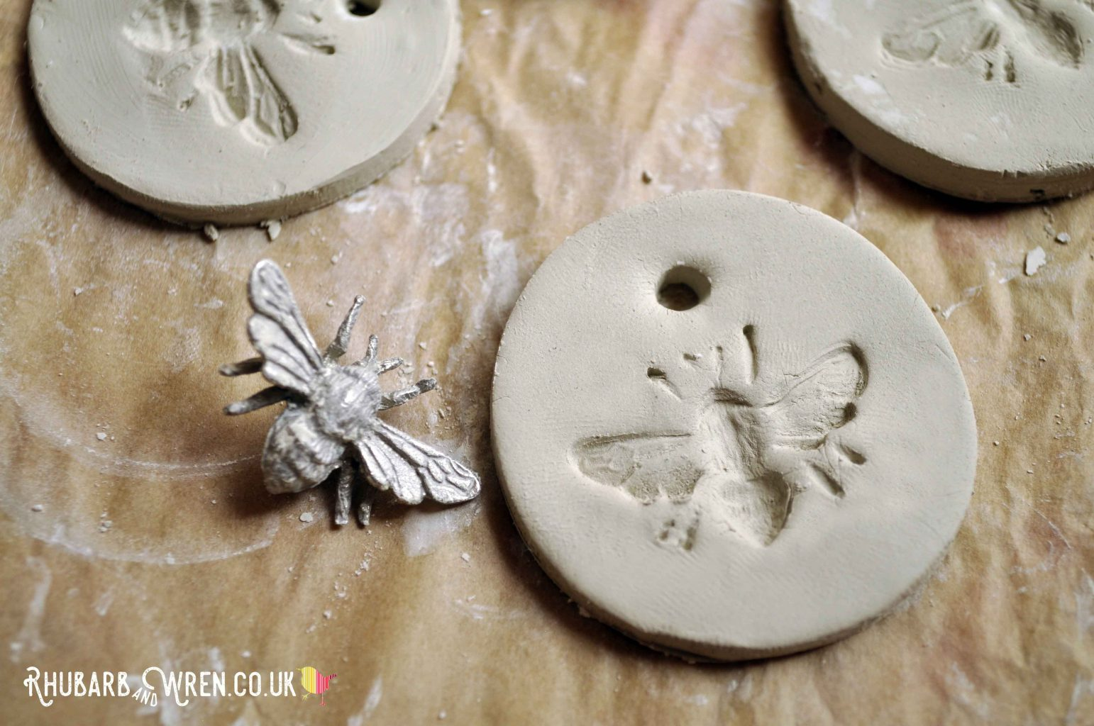 DIY air dry clay pendants drying on greaseproof paper.