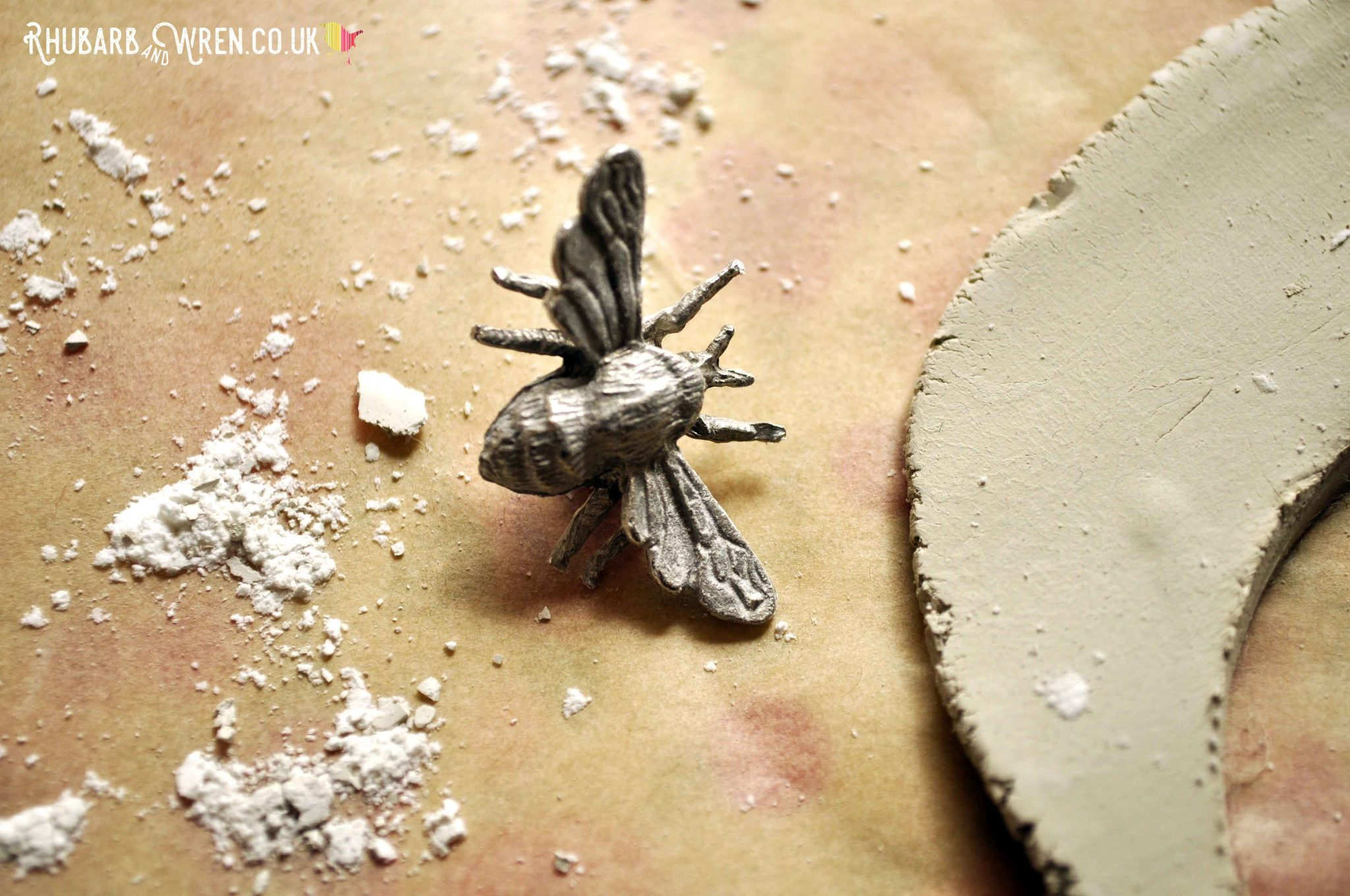 Using a little metal bee to stamp into diy air dry clay pendants